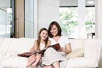 Mother and daughter reading book in living room portrait (thumbnail)