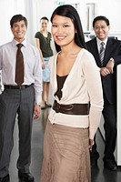 Business woman standing in front of colleagues in office portrait