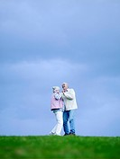 Senior couple embracing outdoors low angle view (thumbnail)