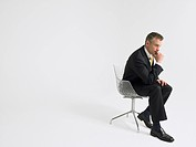 Business man sitting in chair in studio