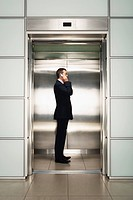 Businessman Using Cell Phone in Elevator side view