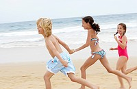 Children holding hands running along sandy beach side view