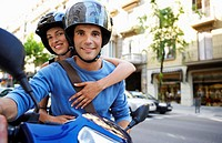 Young couple on motor scooter portrait