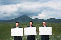 Three smiling businessmen standing in mountain field holding blank signs front view