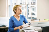 Middle_aged female office worker leaning on cubicle in office holding paperwork
