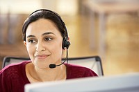 Mid_adult female office worker sitting in cubicle wearing headset portrait