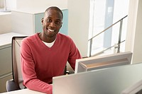 Mid_adult male office worker working at desk portrait