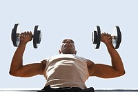 Man Lifting dumbbells low angle view close up