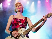 Young Woman playing guitar in concert on stage low angle view