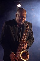 Jazz musician playing saxophone on smokey nightclub stage (thumbnail)