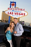 Couple getting out of limousine man holding empty glass in front of Welcome to Las Vegas sign (thumbnail)