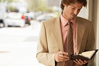 Businessman reading diary in street close_up