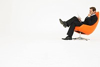 Businessman reading in chair on white background (thumbnail)