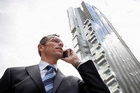Businessman using mobile phone in front of tall building low angle view