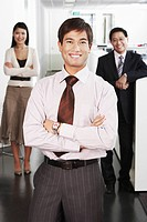 Business man standing in front of colleagues in office portrait (thumbnail)
