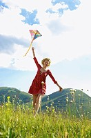 Woman Flying Kite in mountain field front view