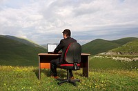 Businessman Sitting at Desk using laptop in mountain field back view