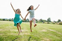 Girls Running and jumping Hand in Hand through field