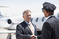 Businessman Beside private jet shaking hands with pilot (thumbnail)