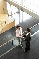 Businessmen shaking hands on Mezzanine elevated view