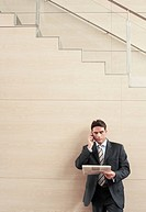 Businessman on cell phone at bottom of stairway half length