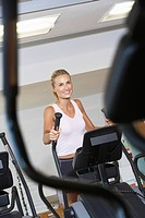 Woman Exercising on Elliptical Machine in health club