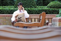 Businessman on park bench reading newspaper and talking on cell phone