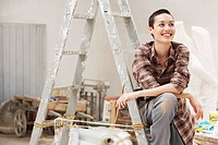 Female interior decorator sitting on ladder in work site front view