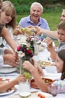 Multigenerational family dining in garden