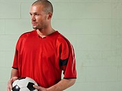 Soccer player holding ball portrait