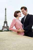 France Paris Couple embracing with Eiffel Tower in distance