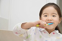 Young Girl in pyjamas Brushing Her Teeth