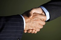 Middle_aged businessmen shaking hands close_up