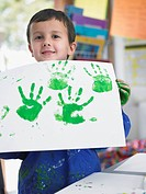 Boy presenting his finger painting in art class (thumbnail)
