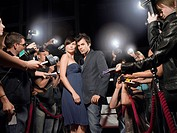 Couple posing on red carpet being photographed by paparazzi