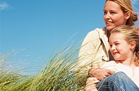Happy mother and daughter sitting together in long grass against blue sky (thumbnail)