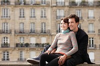 Young couple posing on bridge in front of town houses