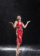 Woman arms raised smiling standing in rain