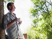 Mature man drinking tea leaning on tree looking at view profile