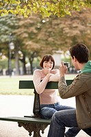 Young man photographing young woman on bench in park (thumbnail)