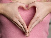 Woman making heart shape with hands close-up mid section (thumbnail)