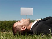Young man lying on grass by blank sign