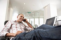 Casually dressed Businessman reclining with feet on desk talking on phone