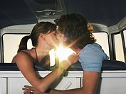 Young couple kissing in front seat of camper van