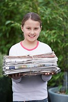 Girl 10_12 holding bundle of waste paper smiling
