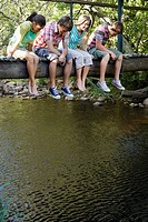 Four teenagers 16-17 years sitting on wooden bridge looking down at stream smiling (thumbnail)