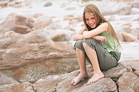 Girl 10_12 sitting on rock on beach portrait