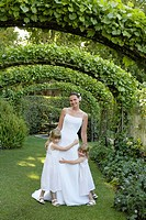 Two young girls embracing mid adult bride under ivy arches portrait