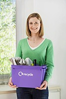 Mid_adult woman holding recycling container smiling