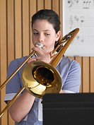 High school girl playing trombone in class portrait